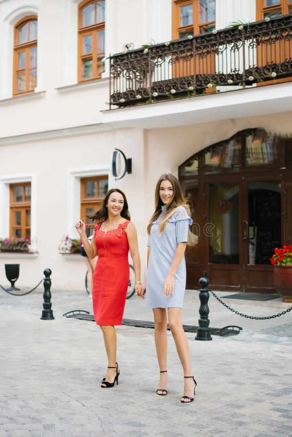 Happy relationship between mother and adult daughter. They walk around the city, holding hands stock photography