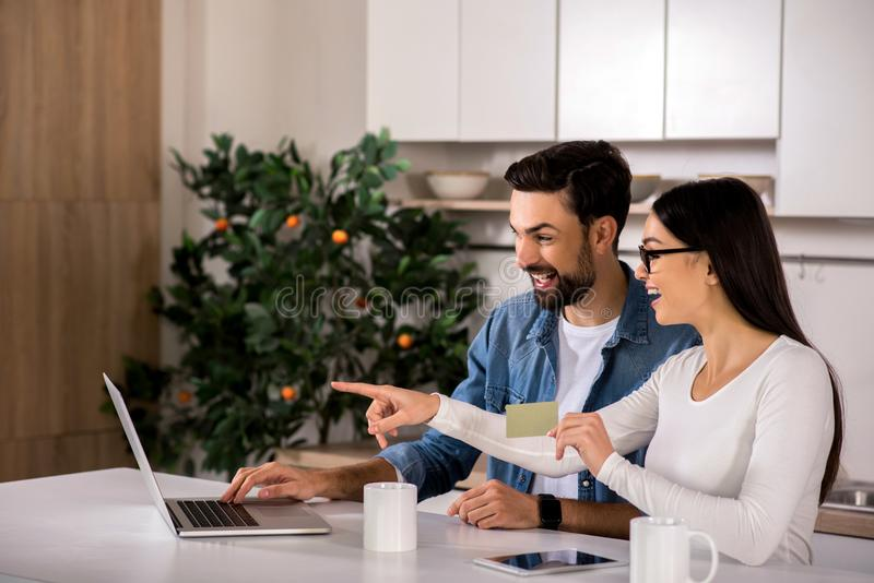 Positive young couple using their laptop. Happy relationships. Cheerful young couple sitting in the kitchen while using their laptop stock photo