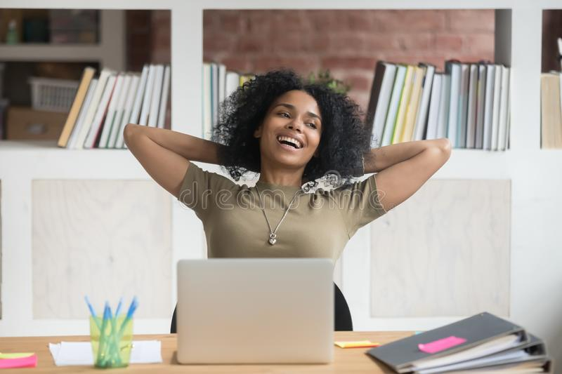 Happy relaxed african american female worker satisfied with finished work. Happy relaxed african female worker student satisfied with finished work study at stock photo