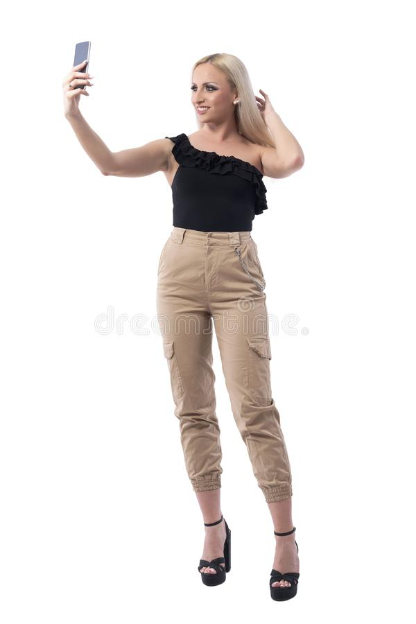 Happy relaxed beautiful blonde young woman adjusting hair posing for selfie. stock photography
