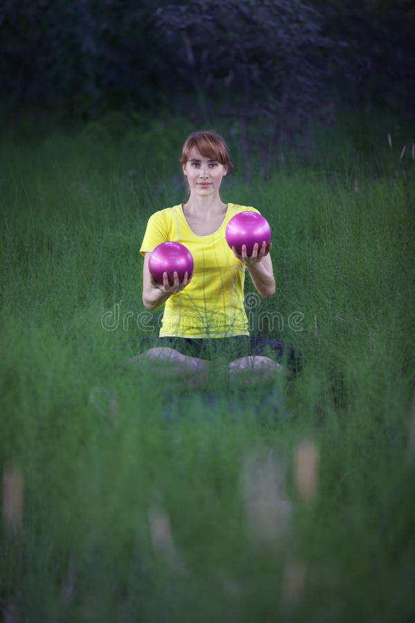 woman in yoga position, raising silver fitness balls stock images