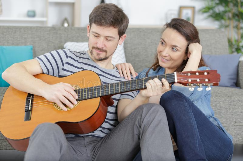 Happy relaxed couple with guitar sitting on couch at home stock images