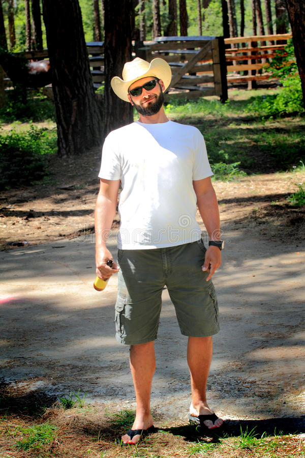 Happy Relaxed Cowboy. A happy relaxing day off for a cowboy standing wearing a white straw western hat, shorts and flip flops, drink in hand with funny royalty free stock photo