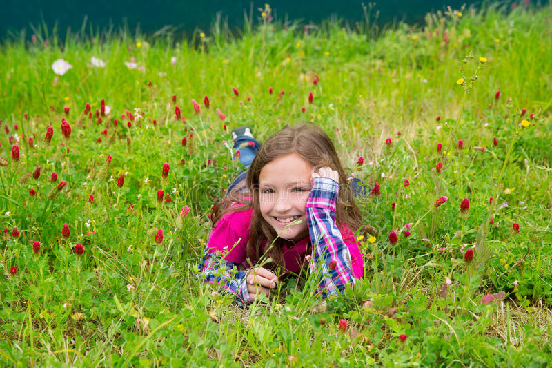 Happy relaxed kid girl on a spring flowers meadow royalty free stock photo