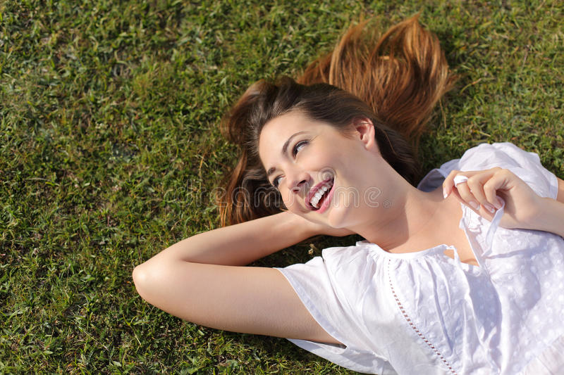 Happy relaxed woman lying on the grass stock photo
