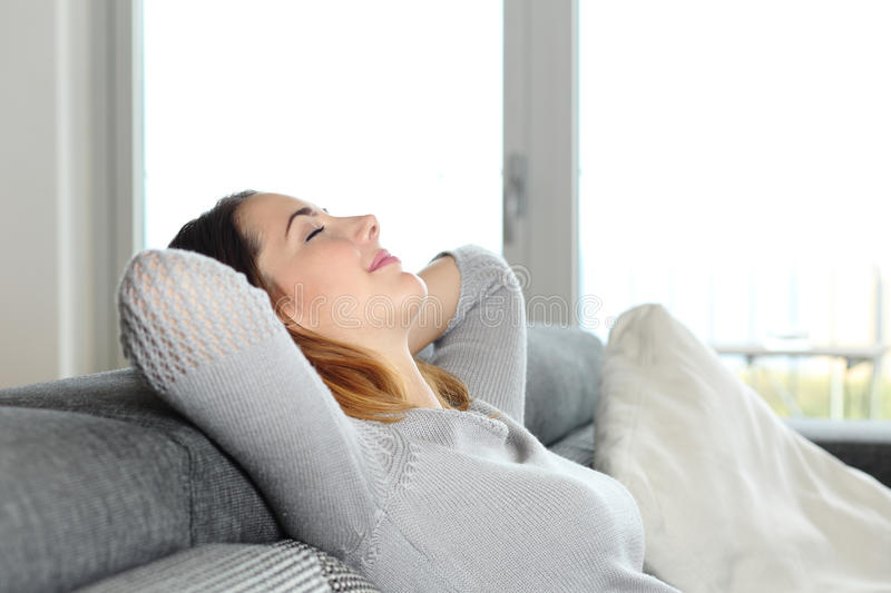 Happy relaxed woman resting on a couch at home. With arms in the head royalty free stock photos