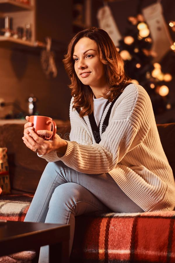Happy relaxed woman in warm sweater holds mug with hot coffee in decorated room at Christmas time. royalty free stock photos