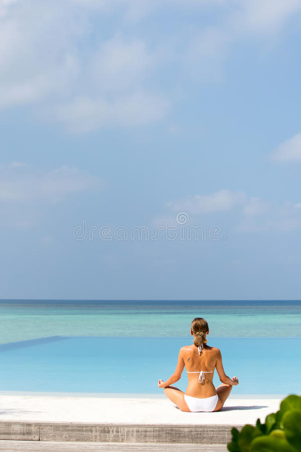 Happy relaxed young woman practicing yoga outdoors at white beach royalty free stock photography