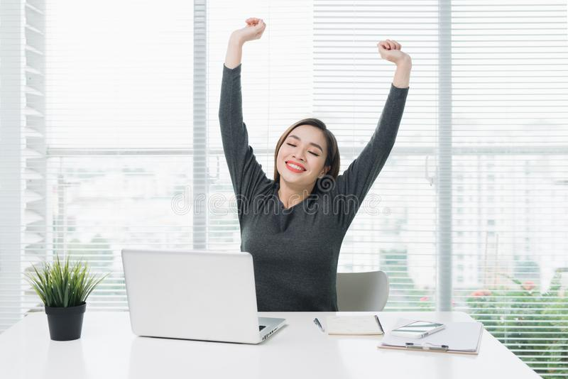 Happy relaxed young woman sitting at her desk with a laptop, stretching her arms stock photos