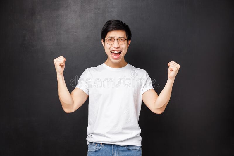 Happy relieved and satisfied young asian guy congratulate his team with win, achieve goal, clench hands like champion. Celebrate success saying yes, triumphing royalty free stock image