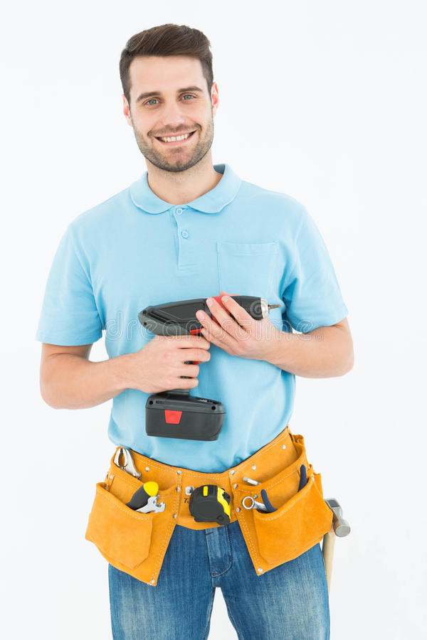 Happy repairman holding hand drill. Portrait of happy repairman holding hand drill against white background royalty free stock image