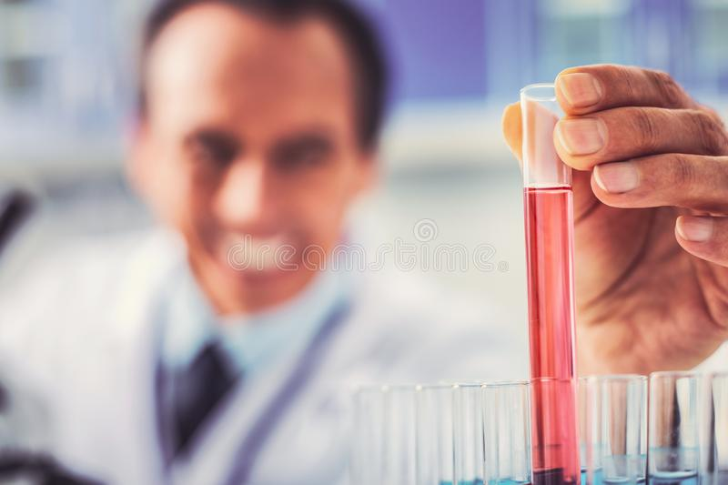 Happy researcher holding important test tube for discovery. Important discovery. Happy skillful researcher feeling emotional while holding important test tube royalty free stock image