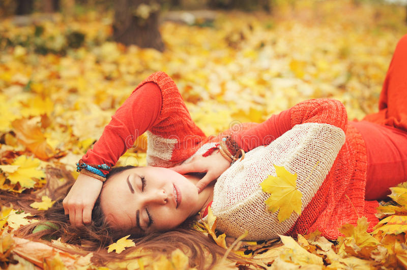 Happy resting girl portrait, lying in autumn maple leaves in park, closed eyes, dressed in fashion sweater. And many friendship bracelets, outdoor stock photography