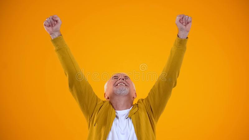 Happy retired man stretching hands up, celebrating success on orange background stock photos