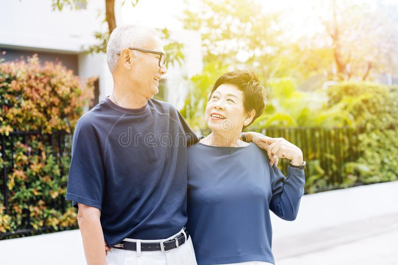 Happy retired senior Asian couple walking and looking at each other with romance in outdoor park and house in background. royalty free stock photos