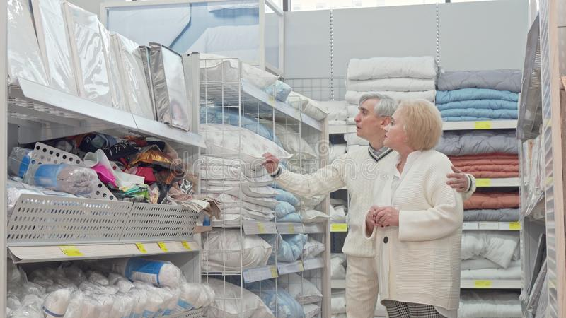 Happy retired senior couple walking in furnishings store, shopping for home goods. Elderly women and her husband choosing textile for home. Retirement royalty free stock photo