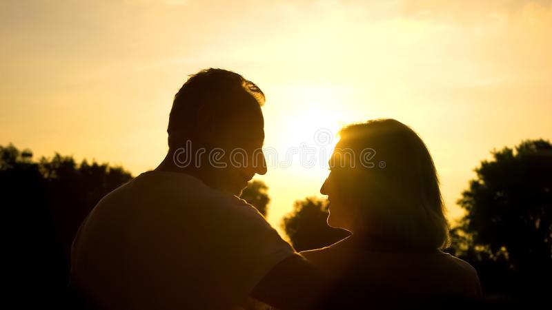 Happy retired spouse looking each other, spending time together in sunset park stock photos