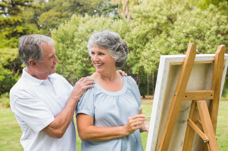 Happy retired woman painting on canvas with husband. Happy retired women painting on canvas with husband in the park on sunny day stock photos