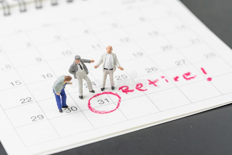 Happy retirement, wealth plan for life after retire from work concept, group of miniature happy senior old men standing with. Circle on white calendar with stock photo