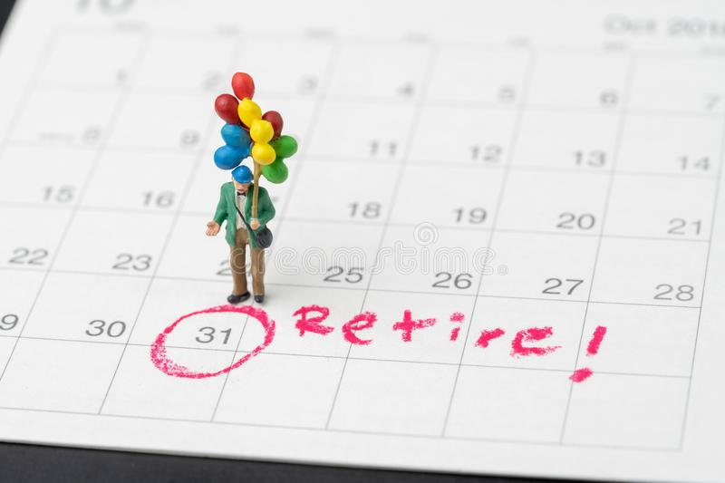 Happy retirement, wealth plan for life after retire from work concept, miniature happy senior old man holding colorful balloons royalty free stock photos