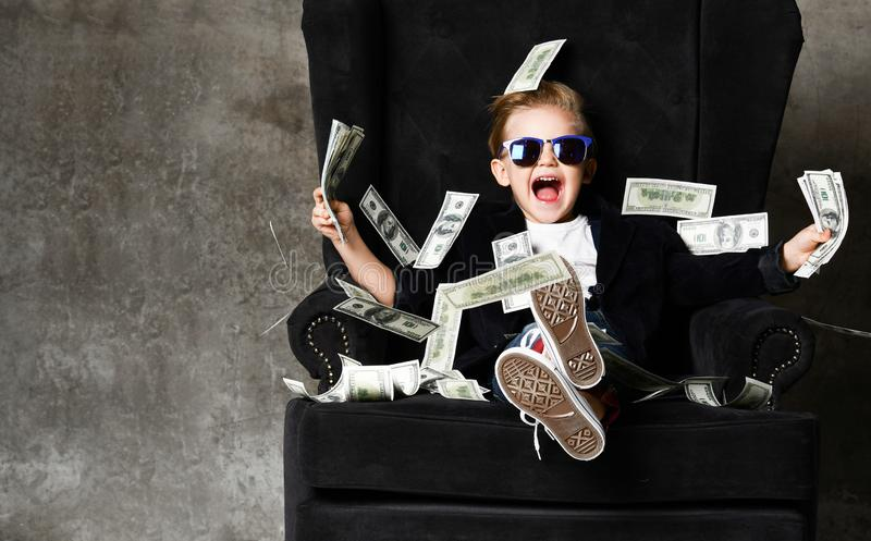 Happy rich kid boy millionaire sits in luxury armchair with bundles of dollars cash in his hands under money rain bills falling. Happy rich kid boy millionaire royalty free stock images