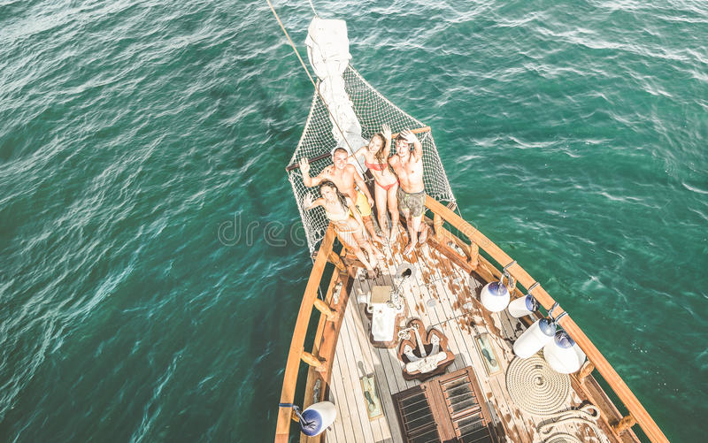 Happy rich multicultural friends having fun at sail boat trip royalty free stock photo