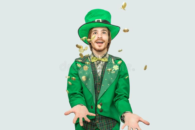 Happy rich young man in saint Patrick`s suit spreading golden coins up and smiling. They fly. Guy look up. on. Grey background royalty free stock image