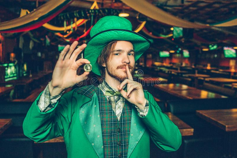 Happy rich young man in St. Patrick`s suit stand in pub and hold golden coin. He has finger close to mouth. Guy look on stock photos
