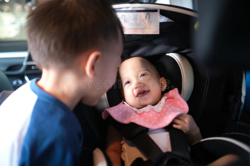 Happy road trip with young kid, Big brother and little sister playing together in car, Cute smiling Asian baby girl child sitting. In rear facing car seat royalty free stock images