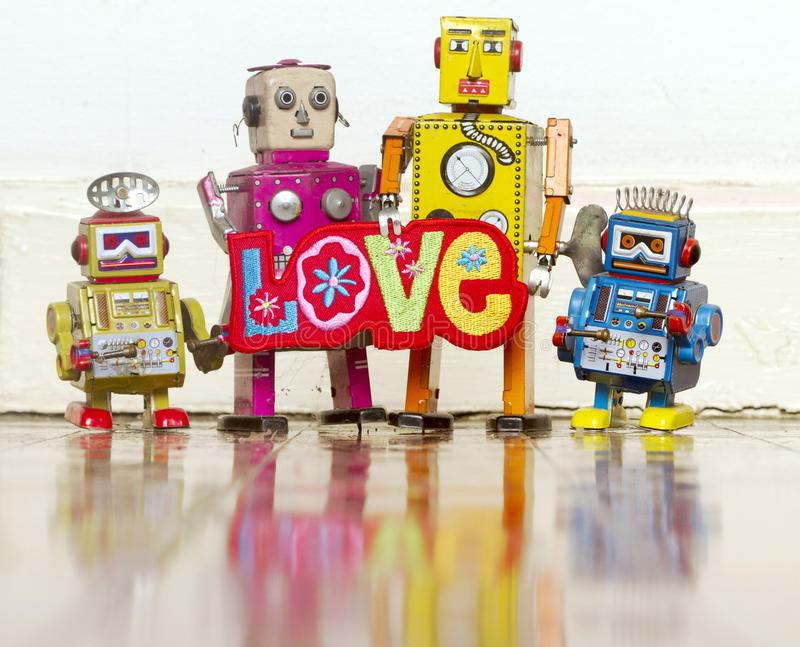 Happy robot family with a bright color cloth love sign stock photo