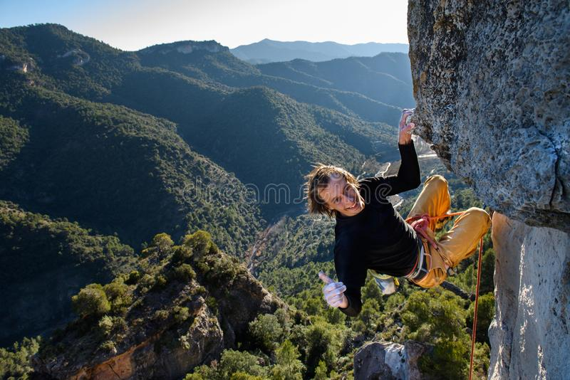 Happy rock climber ascending a challenging cliff.Extreme sport c stock photography