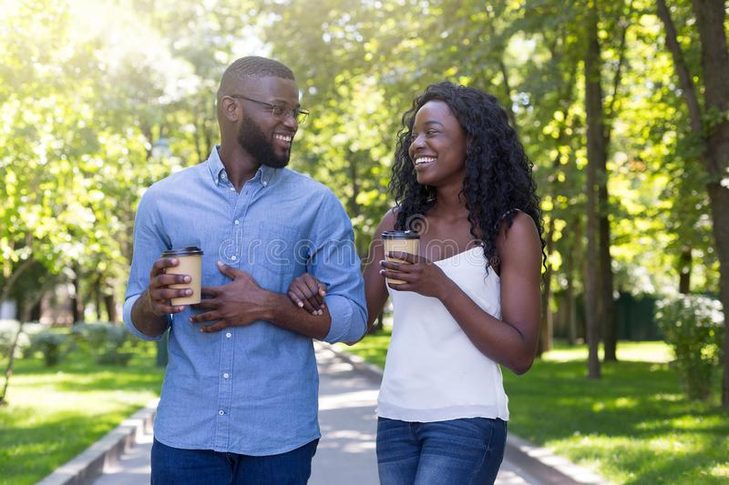 Happy romantic african couple in love walking with cups of coffee enjoying time together stock image