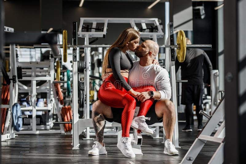 Happy romantic athletic couple. Slender beautiful girl sits on the knees of strong athletic man and kissing in the stock image