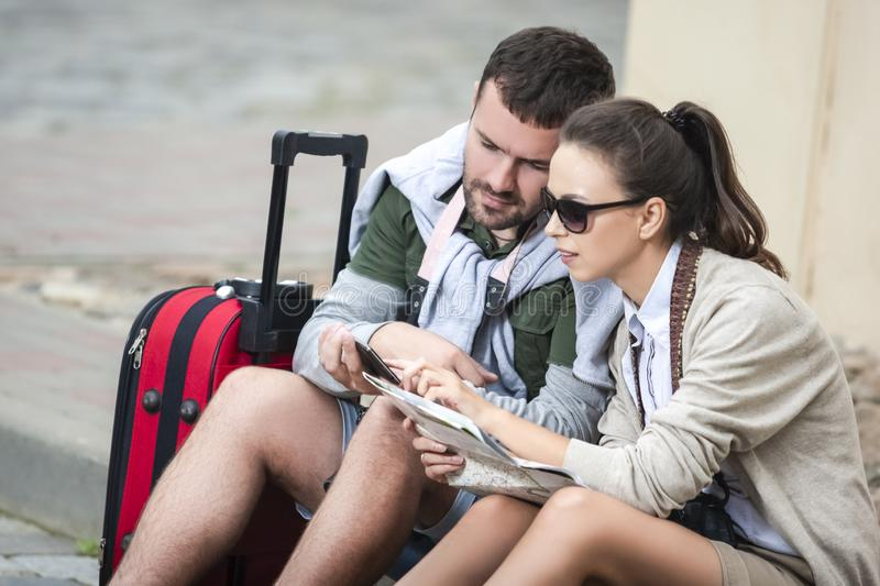 Happy Romantic Caucasian Couple Having a Trip Around the Town. Sitting on Floor and Examining the Map Together stock image