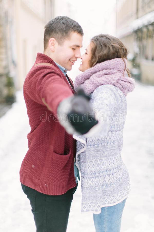 Happy and romantic caucasian couple in warm sweaters walking in winter city Lviv. Holidays, christmas, winter, love, hot royalty free stock photo
