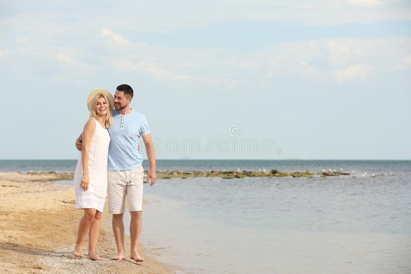 Happy romantic couple  on beach, space for text royalty free stock photo