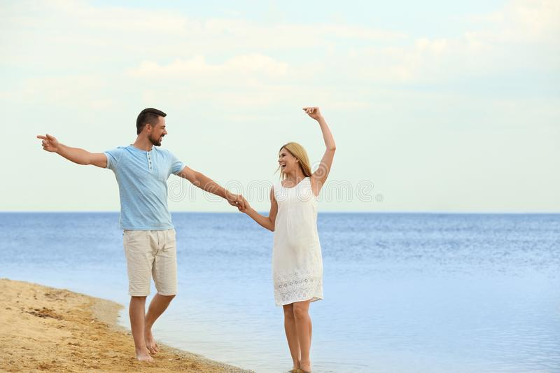 Happy romantic couple dancing on beach. Space for text royalty free stock photography