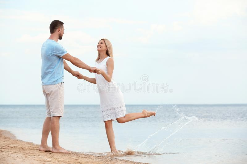 Happy romantic couple dancing on beach royalty free stock photography