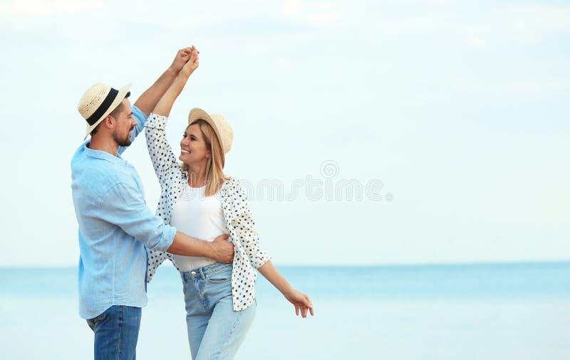 Happy romantic couple dancing on beach royalty free stock image
