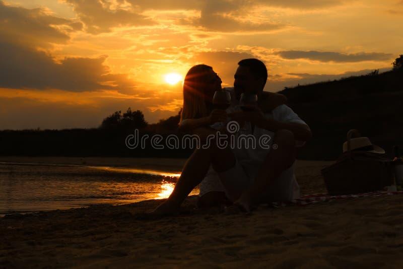 Happy romantic couple drinking wine  on beach. Happy romantic couple drinking wine together on beach stock photo