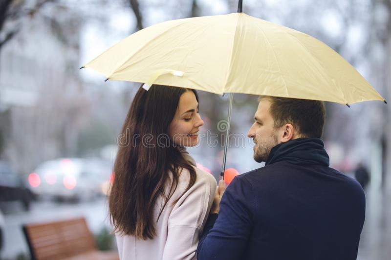 Happy romantic couple, guy and his girlfriend dressed in casual clothes walk under the umbrella and look at each other royalty free stock photos
