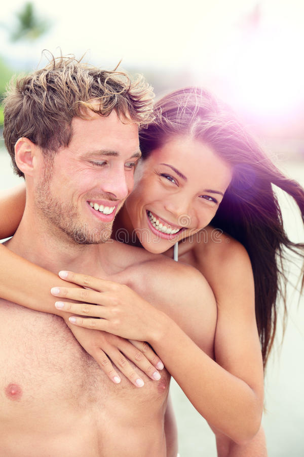 Happy romantic couple lovers on beach honeymoon. Having playful fun together during summer beach holidays. Cheerful young multiracial couple, Asian women and royalty free stock images
