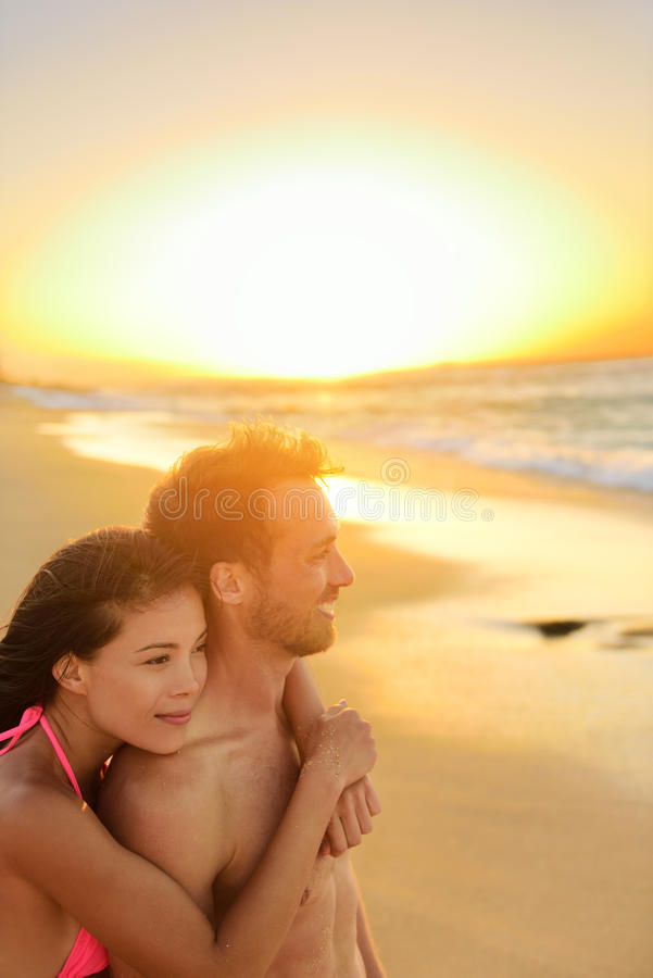 Happy romantic couple lovers on beach honeymoon. Having playful fun together during summer beach holidays. Cheerful young multiracial couple, Asian women and royalty free stock photo