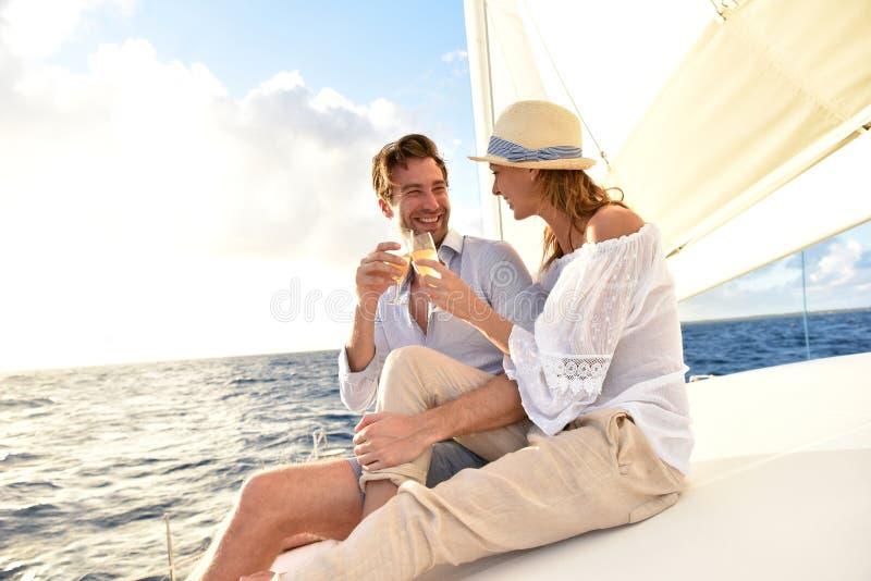 Happy romantic couple making toast on sailing cruise stock image