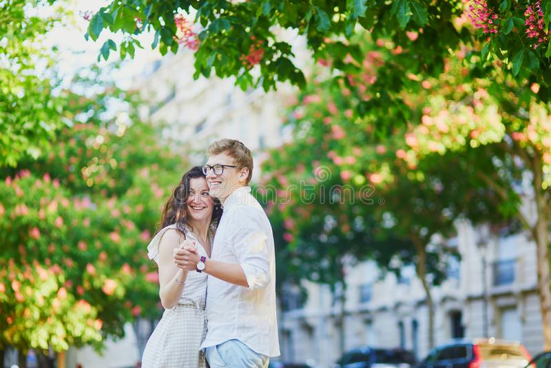 Happy romantic couple in Paris, hugging under pink chestnuts in full bloom royalty free stock image