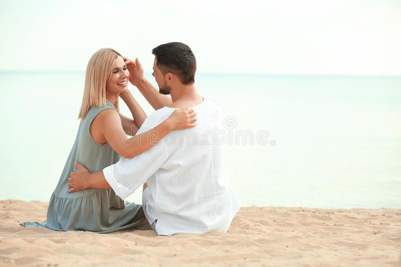 Happy romantic couple sitting on beach royalty free stock image