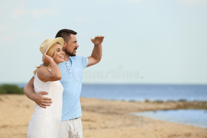 Happy romantic couple spending time together on beach stock photo