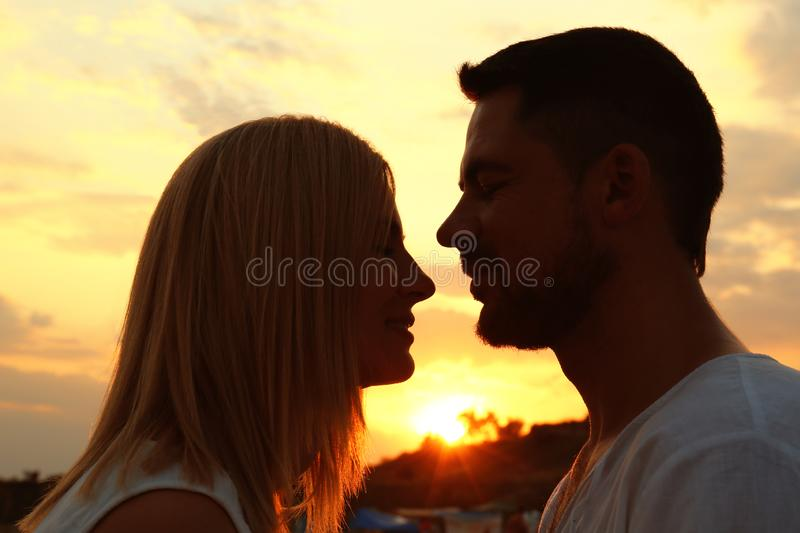 Happy romantic couple spending time together at sunset. Happy romantic couple spending time together on beach at sunset royalty free stock images
