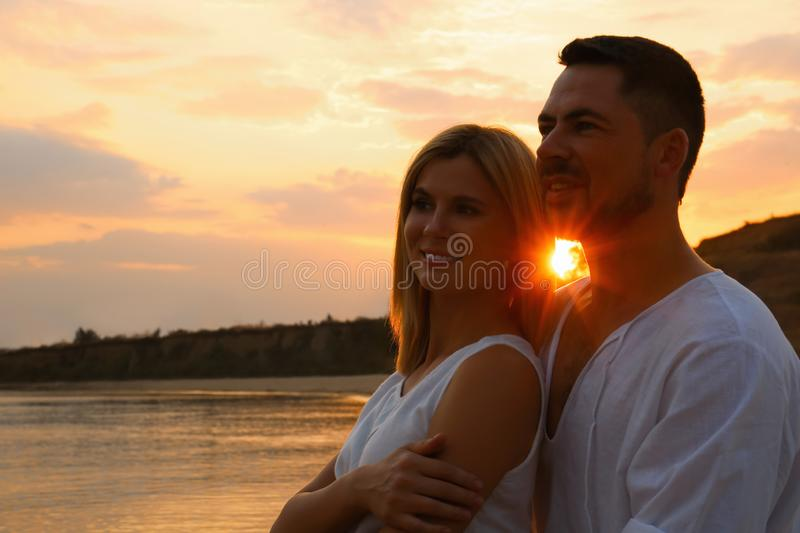 Happy romantic couple spending time together on beach at sunset. Space for text royalty free stock image