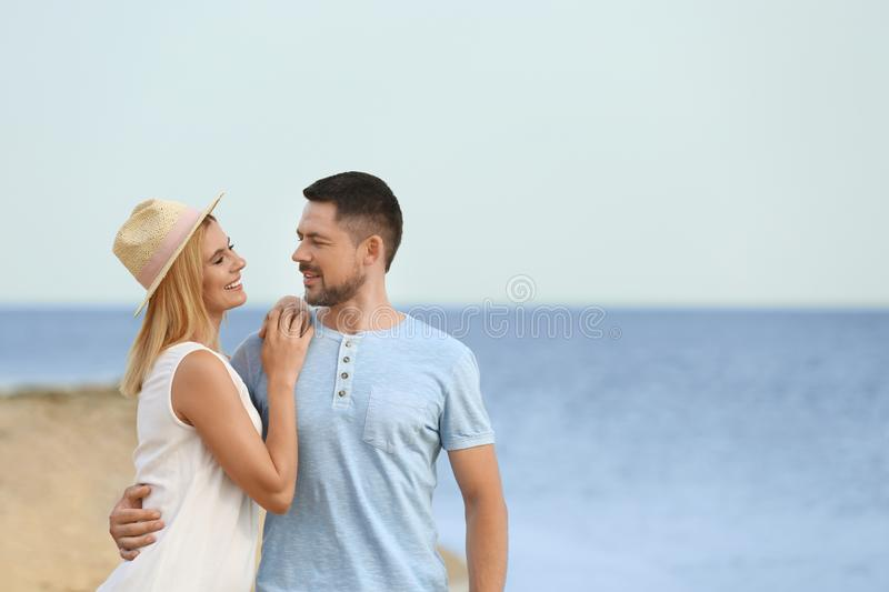 Happy romantic couple  time together on beach, space for text stock photos
